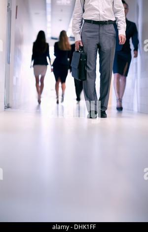Vista bassa delle persone che camminano giù il corridoio in un edificio per uffici Foto Stock