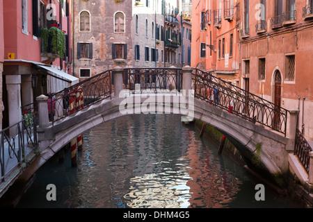 Splendido piccolo ponte su un piccolo canale foderato con i suoi edifici colorati a Venezia, Italia Foto Stock