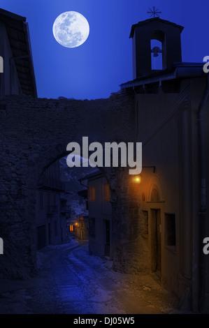 Vista notturna di strada stretta tra le vecchie case sotto il cielo con la luna piena in città di tende, Francia. Foto Stock