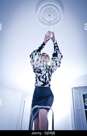 Donna cambiare la lampadina di luce in una stanza