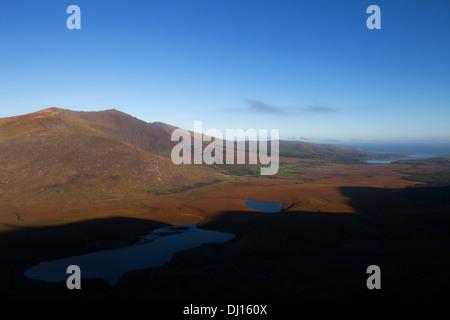 Laghi sotto il Conor Pass con Brandon Mountain e distante Castlegregory, penisola di Dingle, nella contea di Kerry, Foto Stock