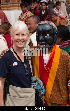 Il Bhutan, Thimpu Dzong, Tsechu annuale senior donna occidentale turistico con atsara clown Foto Stock