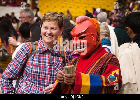 Il Bhutan, Thimpu Dzong, annuale Tsechu femmina turista occidentale con atsara clown ballerina azienda soldi in Foto Stock