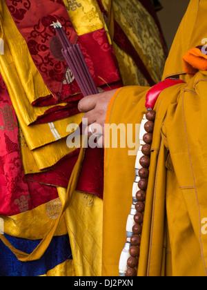Il Bhutan, Thimpu Dzong, Tsechu annuale, le mani del monaco holding di fumare bastoncini di incenso Foto Stock