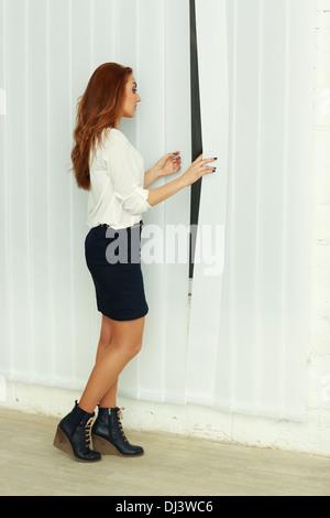 Giovane imprenditrice guardando nella finestra di office Foto Stock