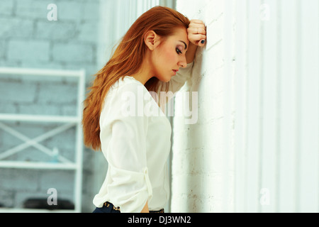 Stanco giovane imprenditrice leaing presso la parete in ufficio Foto Stock