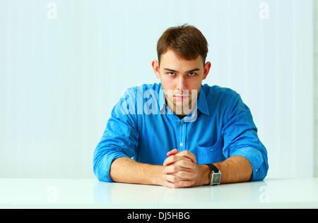 Ritratto di un giovane imprenditore fiducioso seduta al tavolo in ufficio Foto Stock