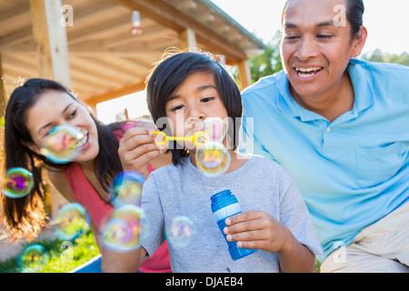 Famiglia soffiare bolle all'aperto Foto Stock