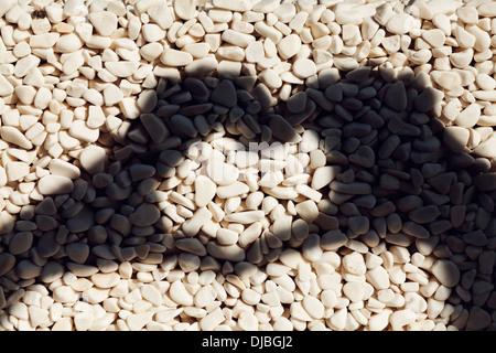 Forma di cuore di mano d'ombra su ciottoli ovale Foto Stock