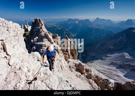 L'alpinista salendo la Via Ferrata Marino Bianchi arrampicata sul cristallo di mezzo Montagna Dolomiti a Belluno Foto Stock