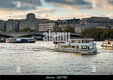 Il Tamigi crociere di piacere passare sotto il ponte di Waterloo; landmark building Shell - Mex House costituisce Foto Stock