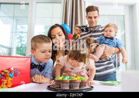 Famiglia guardando la ragazza soffiando le candeline sulla torta di compleanno Foto Stock