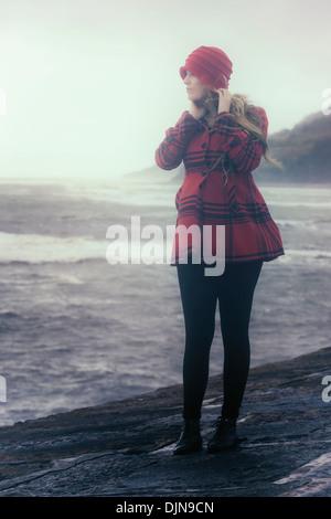Una donna in un rosso di rivestimento è in piedi su un vecchio molo di pietra Foto Stock