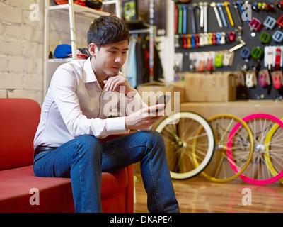 Giovane uomo seduto nel negozio di biciclette tramite telefono cellulare Foto Stock