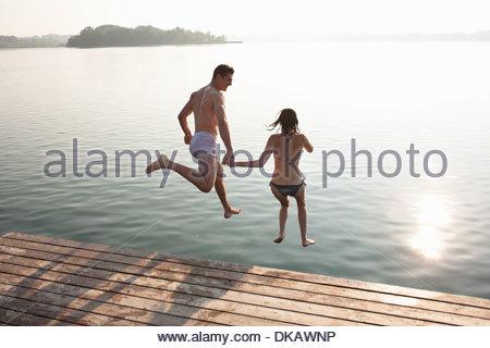 Coppia giovane salta fuori il lago di pier Foto Stock