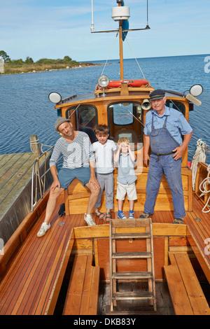 Padre e due figli con il pescatore sulla barca, Eggergrund, Svezia Foto Stock