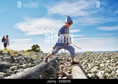 Ragazzo vestito come pirati stepping in tronchi di legno sulla spiaggia, Eggergrund, Svezia Foto Stock