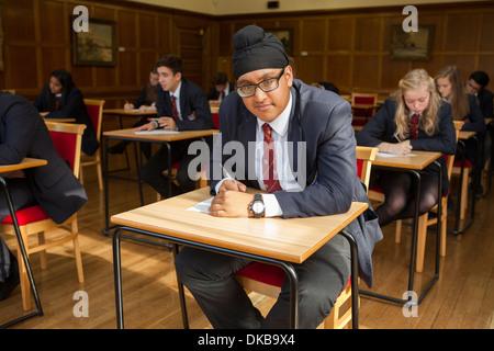 Gruppo di scolari adolescenti facendo exam Foto Stock