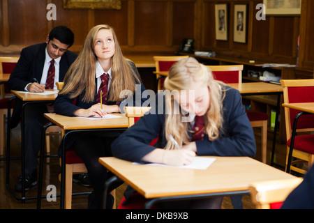 Gruppo di scolari adolescenti seduta esame Foto Stock