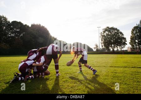 Teenage schoolboy rugby tenendo palla da huddle Foto Stock