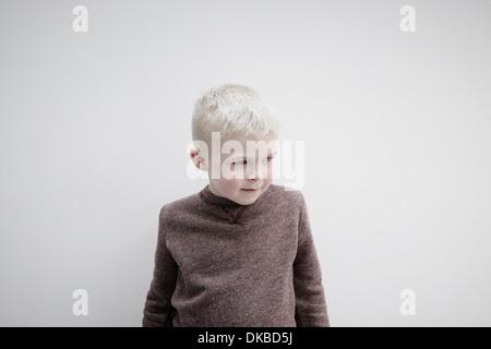 Ritratto di ragazzo indossa ponticello marrone, guardando lontano Foto Stock