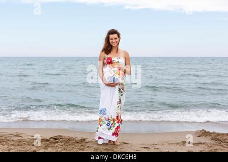 Donna incinta in piedi sulla spiaggia, mani su stomaco Foto Stock