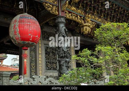 Grande lanterna rossa, un albero e una facciata ornata di Mengjia tempio Longshan in Taipei, Taiwan Foto Stock