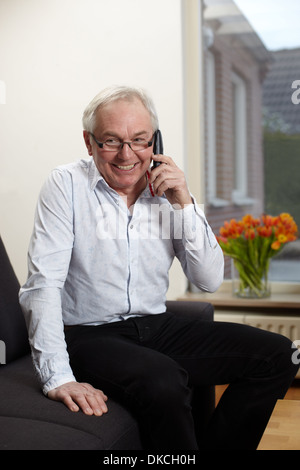 Senior uomo a casa parlando al telefono cellulare Foto Stock
