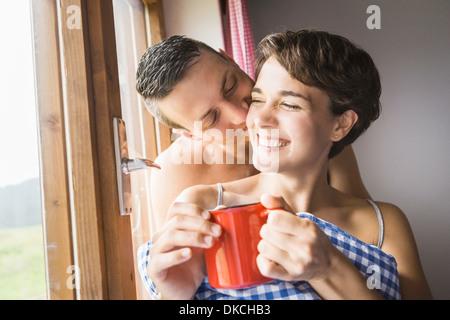 Coppia giovane la condivisione di un bacio in vacanza chalet, Tirolo, Austria Foto Stock