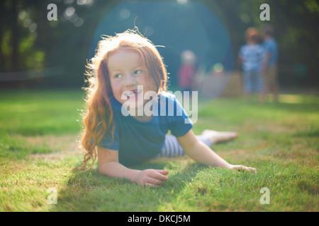 Felice giovane ragazza distesa su erba in giardino Foto Stock
