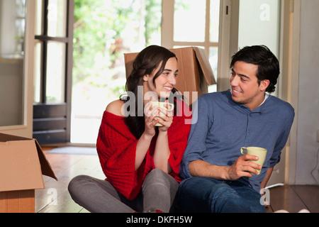 Coppia giovane avente pausa caffè mentre casa in movimento Foto Stock