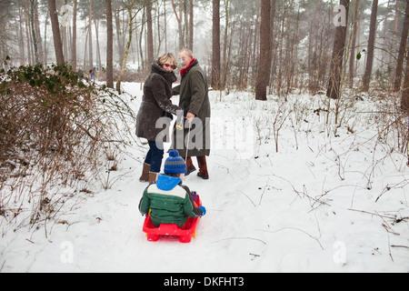 Nonni nipote di trazione sul toboga in snow Foto Stock