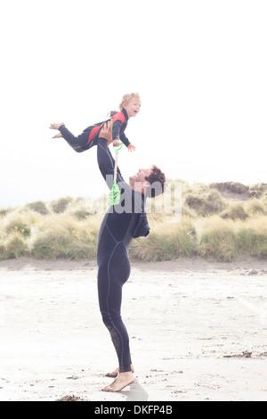 Padre figlio di sollevamento sulla spiaggia Foto Stock