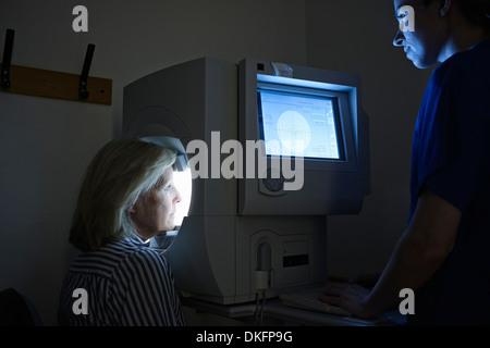 Paziente di sesso femminile avente un esame degli occhi in ospedale Foto Stock