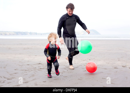 Padre e figlio giocando con palloncini sulla spiaggia Foto Stock