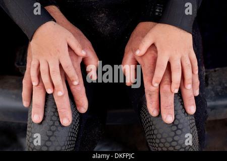 Ragazzo le mani sulla parte superiore del padre con le mani in mano Foto Stock