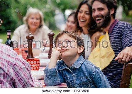 Annoiato ragazzo in outdoor famiglia pasto Foto Stock