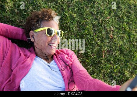 Ritratto di donna senior sdraiati sull'erba indossando occhiali da sole