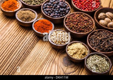 Una selezione di varie spezie colorate su di un tavolo di legno in ciotole Foto Stock