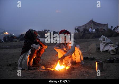 Pushkar, India. Xx Nov, 2012. Camel herders sedere accanto al fuoco la sera nella loro tenda camp durante il tradizionale Foto Stock