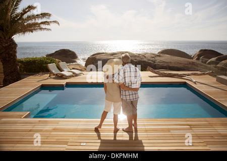 Coppia senior costeggiata dalla moderna piscina che si affaccia sull'oceano Foto Stock