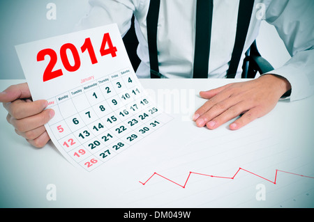 Imprenditore seduto su una scrivania con un grafico e che mostra un calendario 2014 Foto Stock