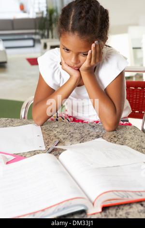Alimentato fino ragazza facendo i compiti in cucina Foto Stock