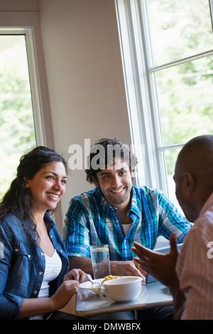 Tre persone sedute a un tavolo del bar di parlare. Foto Stock