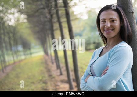 Una donna con le braccia incrociate appoggiata contro un albero. Foto Stock