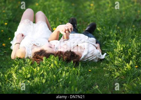 Amare giovane sdraiato su un prato e tenendo le mani Foto Stock