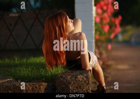 Giovane donna sdraiata su un muro di mattoni sotto la luce diretta del sole Foto Stock