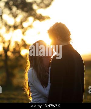 Amare giovane kissing in controluce Foto Stock