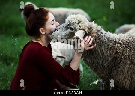 Giovane donna con pecora su un prato Foto Stock
