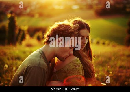 Coppia giovane in amore abbracciando su un prato Foto Stock